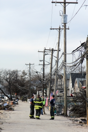 BREEZY POINT, NY - NOVEMBER 20: Firefighters assessing damage in hurricane devastated area  in the aftermath of Hurricane Sandy on November 20, 2012 in Breezy Point, NY. More than 80 houses were destroyed in out-of-control six-alarm blaze.