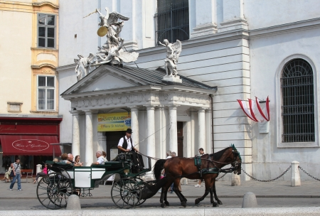 VIENNA, AUSTRIA - SEPTEMBER 3 :Fiaker carriage with  tourists on September 3, 2012 in Vienna, Austria. For many tourists a fieker ride is the most popular attraction in Vienna.
