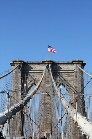 American flag on top of the famous Brooklyn Bridge