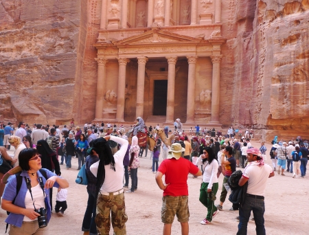 PETRA, JORDAN - NOVEMBER 16: Numerous tourists in  front of the ancient Treasury on November 16, 2010 in Petra, Jordan.  Petra has been a UNESCO World Heritage Site since 1985