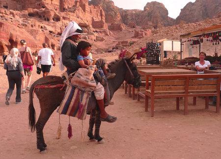 east riding: PETRA, JORDAN - NOVEMBER 16: Bedouin on donkey with child  on November 16, 2010 in Petra, Jordan.  Petra has been a UNESCO World Heritage Site since 1985