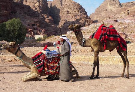 east riding: PETRA, JORDAN - NOVEMBER 16: Bedouin with camels on November 16, 2010 in Petra, Jordan.  Petra has been a UNESCO World Heritage Site since 1985