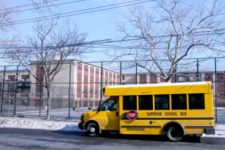 BROOKLYN, NEW YORK - FEBRUARY 14: School bus in front of public school in Brooklyn, NY on February 14, 2013. NYC School Bus Drivers union 1181 still on strike form January 16, 2013.