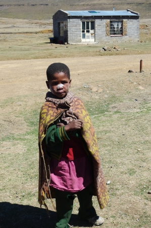 landlocked: SANY PASS,LESOTHO - SEPTEMBER 19:Unidentified boy at Sani Pass, Lesotho on September 19, 2009 at an altitude of 2 874m. Lesotho, officially the Kingdom of Lesotho, is a landlocked country and enclave. Editorial