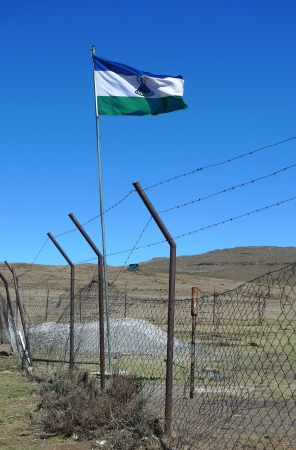 landlocked: SANY PASS,LESOTHO -SEPTEMBER 19:Kingdom of Lesotho flag flying at the border between South Africa and Lesotho on September 19, 2009. The Kingdom of Lesotho is a landlocked country and enclave.   Editorial