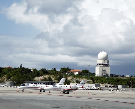 PRINCESS JULIANA AIRPORT, ST MAARTEN - NOVEMBER 9: Private jets and traffic control tower in Princess Juliana Airport on November 9, 2012. It serves the Dutch part of the island of Saint Martin.