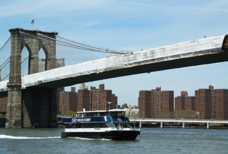 NEW YORK - APRIL 30: East River ferry boat under Brooklyn Bridge on April 30, 2013.  East River Ferry features frequent, reliable service that connects Manhattan with various destinations in NYC