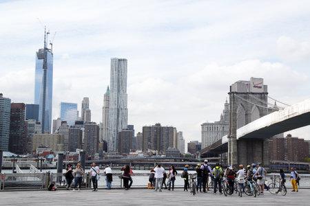 guia turistico: NUEVA YORK - 07 de mayo: Excursi�n de la bici con el gu�a tur�stico bajo Puente de Brooklyn, el 7 de mayo de 2013. El puente de Brooklyn es uno de los puentes colgantes m�s viejos de los EE.UU. se complet� en 1883 Editorial