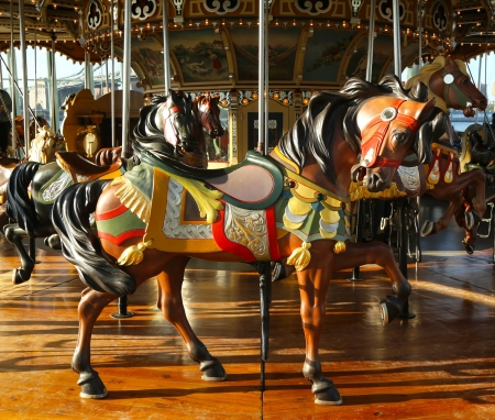 Horses on a traditional fairground carousel photo