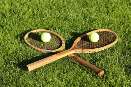 Old tennis rackets on grass court photo