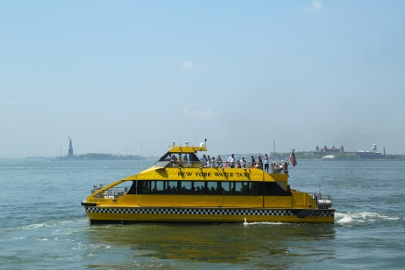 NEW YORK - MAY 21: New York City Water Taxi in the front of Statue of Liberty and Ellis Island  on May 21, 2013. NYC Water Taxi has been servicing NYC commuters since 2002