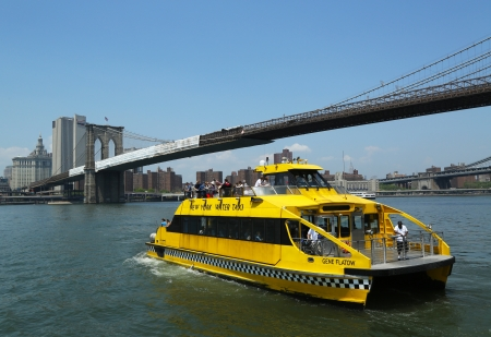 NEW YORK - MAY 21: New York City Water Taxi under Brooklyn Bridge on May 21, 2013. NYC Water Taxi offering commuter and sightseeing service along the East River and Hudson River
