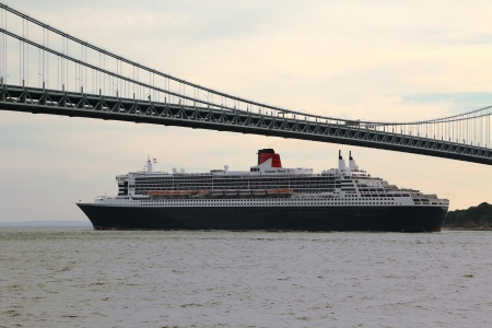NEW YORK CITY - JULY 27: Queen Mary 2 cruise ship in New York Harbor under Verrazano Bridge heading for Transatlantic Crossing  from New York to  Southampton on July 27, 2013
