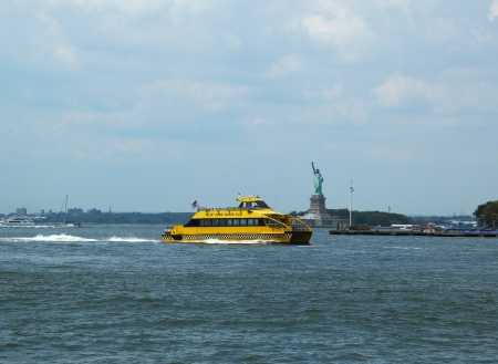 NEW YORK - JULY 27: New York City Water Taxi in the front of Statue of Liberty on July 27, 2013. NYC Water Taxi has been servicing NYC commuters since 2002