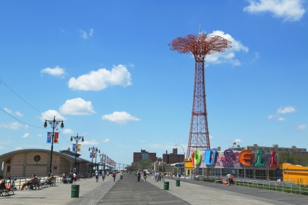 BROOKLYN, NEW YORK - JULY 30: Coney Island Boardwalk, parachute jump tower and restored historical B&B carousel in Brooklyn on July 30, 2013. Jump tower has been called the Eiffel Tower of Brooklyn Editorial