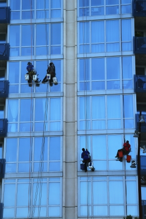 Four window washers on skyscraper photo