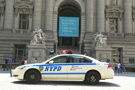 new world order: NEW YORK - AUGUST 6  NYPD car in the front of National Museum  of the American Indian in Manhattan on August 6, 2013  NYPD on high alert after terror threat in New York City