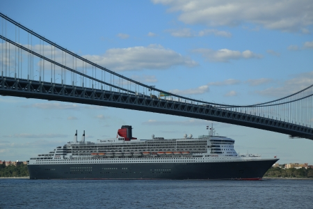 NEW YORK CITY - AUGUST 15  Queen Mary 2 cruise ship in New York Harbor under Verrazano Bridge heading for Transatlantic Crossing from New York to Southampton on August 15, 2013