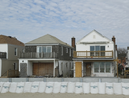 FAR ROCKAWAY, NY - OCTOBER 22  Damaged beach houses in devastated area one year after Hurricane Sandy on October 22, 2013 in Far Rockaway, NY  Notice protective barrier build to prevent flooding