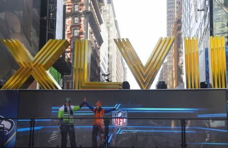 NNEW YORK - JANUARY 30  Seattle Seahawlks and Denver Broncos fans posing for picture next to Roman Numbers on Broadway during Super Bowl XLVIII week in Manhattan on January 30, 2014