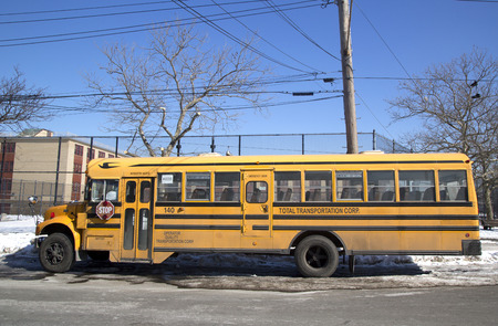 BROOKLYN, NEW YORK - FEBRUARY 11  School bus in the front of public school in Brooklyn, NY on February 11, 2014  New York City has the largest school transportation department in the country