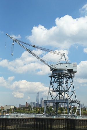 freedom tower: BROOKLYN, NY - AUGUST 17  Dockside crane in Red Hook section of Brooklyn with the view of Freedom Tower and downtown Manhattan at background on August 17, 2013