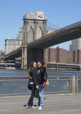 NEW YORK - APRIL 24  Young couple taking selfie in the front of Brooklyn Bridge on April 24, 2014  The Brooklyn Bridge is the one of the oldest suspension bridges in the USA completed in 1883