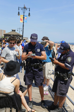 BROOKLYN, NY- JUNE 15 NYPD officers writing ticket for alcohol-related offense at Coney Island Boardwalk  in Brooklyn on June 15, 2014  The NYPD established in 1845, is the largest police force in USA Editorial