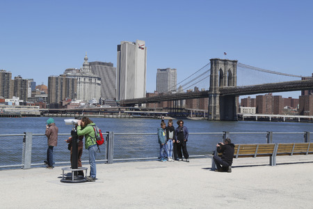 NEW YORK - APRIL 24 Tourists taking pictures in the front of Brooklyn Bridge on April 24, 2014 The Brooklyn Bridge is an icon of New York and was designated a National Historic Landmark in 1964
