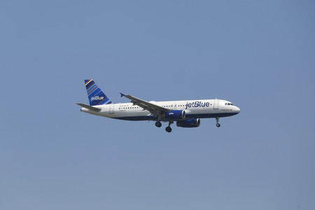 jetblue: NEW YORK - JULY 8 JetBlue Airbus A320 in New York sky before landing at JFK Airport on July 8, 2014  JetBlue Airways is an American low-cost airline with main base at JFK International Airport