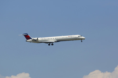 jetblue: NEW YORK - JULY 8  Delta Connection Bombardier CRJ-900 in New York sky before landing at JFK Airport on July 8, 2014  Delta Air Lines and its subsidiaries operate over 5000 flights every day  Editorial