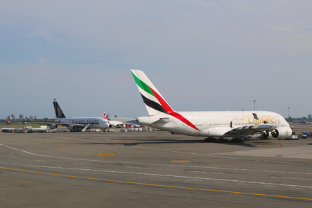 world   s largest: NEW YORK -JULY 10  Emirates Airline and Singapore Airlines Airbus A380 jets at JFK Airport  in NY on July 10, 2014  The Airbus A380 is a double-deck, wide-body, world s largest passenger airliner  Editorial