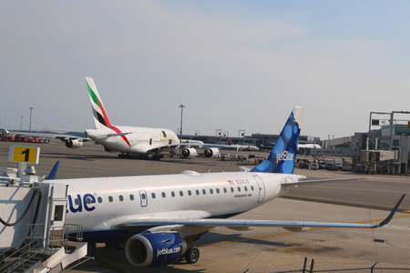 airborne vehicle: NEW YORK- JULY 10  JetBlue Embraer 190 aircraft at the gate at the Terminal 5 and Emirates Airline Airbus A380 at John F Kennedy International Airport in New York on July 10, 2014