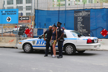 new world order: NEW YORK - JULY 17  NYPD Police Officers taking picture with tourist near World Trade Center  in Manhattan on July 17, 2014 Editorial