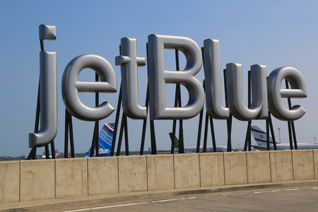 jetblue: NEW YORK- JULY 10  JetBlue sign at the Terminal 5 at John F Kennedy International Airport in New York on July 10, 2014  JFK is one of the biggest airports in the world with 4 runways and 8 terminals