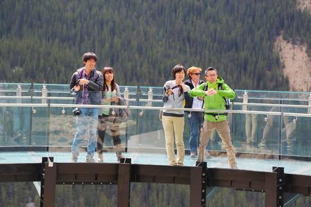 extending: ALBERTA, CANADA - JULY 27 Tourists at the Glacier Skywalk in Jasper National Park on July 27, 2014  The award-winning glass-bottomed observation platform extending 30 metres over the Sunwapta Valley