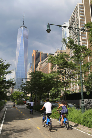 freedom tower: NEW YORK - JULY 17  Unidentified bicycle riders near Freedom Tower in NY on July 17, 2014  Freedom Tower is the tallest building in the Western Hemisphere and the third-tallest building in the world