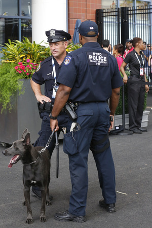 k 9: NEW YORK - AUGUST 23  NYPD transit bureau K-9 police officers and K-9 dog Sam  providing security at National Tennis Center during US Open 2014 on August 23, 2014 in New York Editorial