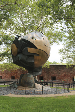 ignited: NEW YORK - JUNE 17: World Trade Center Sphere damaged at September 11 in Battery Park on June 17, 2014. Eternal flame in front of it was ignited on September 11, 2002