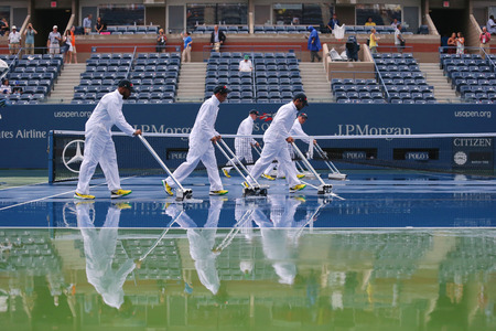 billie: NEW YORK -SEPTEMBER 6: US Open cleaning crew drying tennis court after rain delay at Arthur Ashe Stadium at Billie Jean King National Tennis Center on September 6, 2014 in Flushing, NY Editorial