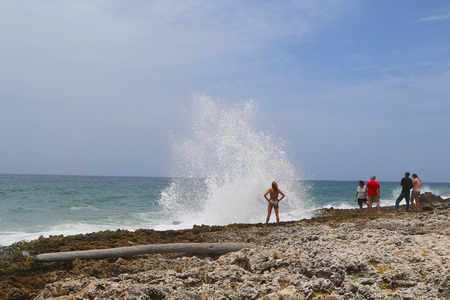 blowhole: GRAND CAYMAN, CAYMAN ISLANDS -June 11: Tourists next to blowhole at Grand Cayman on June 11, 2014. The Cayman Islands are a British Overseas Territory in the western Caribbean Sea. Editorial