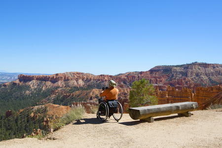 BRYCE CANYON, UTAH - SEPTEMBER 23: Unidentified handicapped visitor at the rim at Bryce Canyon National Park in Utah on September 23, 2014 Imagens - 33075283