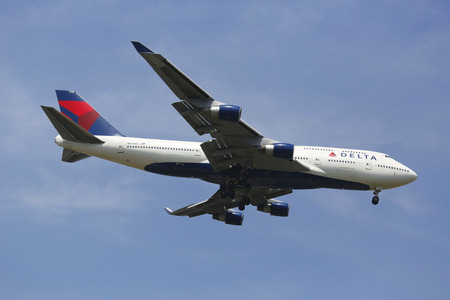 world's: NEW YORK -JULY 8: Delta Airline Boeing 747 in New York sky before landing at JFK Airport on July 8, 2014. The Boeing 747 is a wide-body commercial airliner and the world s most recognizable aircraft