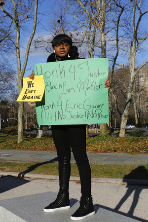 BROOKLYN, NEW YORK - DECEMBER 14: A protester holds a sign during a march against police brutality and grand jury decision on Eric Garner case on Grand Army Plaza in Brooklyn on December 14, 2014