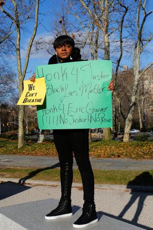 jurado: BROOKLYN, NUEVA YORK - 14 de diciembre: Un manifestante sostiene un cartel durante una marcha contra la brutalidad policial y la gran decisi�n del jurado en caso Eric Garner en Grand Army Plaza en Brooklyn el 14 de diciembre 2014