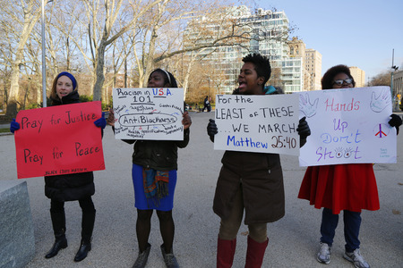 BROOKLYN, NEW YORK - DECEMBER 14: A protesters hold a signs during a march against police brutality and grand jury decision on Eric Garner case on Grand Army Plaza in Brooklyn on December 14, 2014
