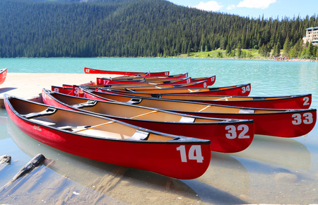 louise: LAKE LOUISE, CANADA - JULY 27:Canoes on beautiful turquoise Lake Louise on July 27, 2014. Lake Louise is the second most-visited destination in the Banff National Park. Editorial