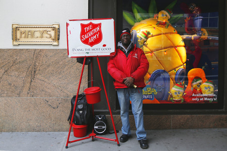 singing bells: NEW YORK - DECEMBER 18: Salvation Army soldier near Macy s  on December 18, 2014 in midtown Manhattan. This Christian organization is known for its charity work, operating in 126 countries