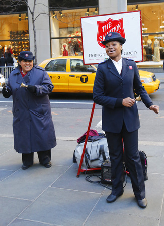 singing bells: NEW YORK - DECEMBER 18: Salvation Army soldiers performs for collections on December 18, 2014 in midtown Manhattan. This Christian organization is known for its charity work, operating in 126 countries