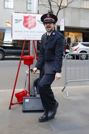 singing bells: NEW YORK - DECEMBER 18: Salvation Army soldier performs for collections on December 18, 2014 in midtown Manhattan. This Christian organization is known for its charity work, operating in 126 countries Editorial